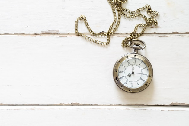 Beautiful bronze watch necklace on white wooden floor.