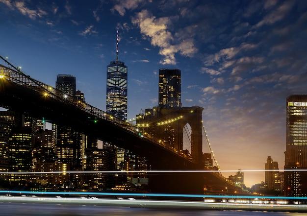 ニューヨーク市マンハッタンのミッドタウンからの美しいブルックリン橋、日没の米国で見られるライト