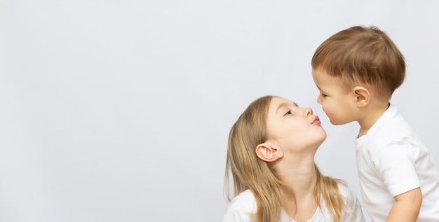 Beautiful brother and sister kiss with copy space banner