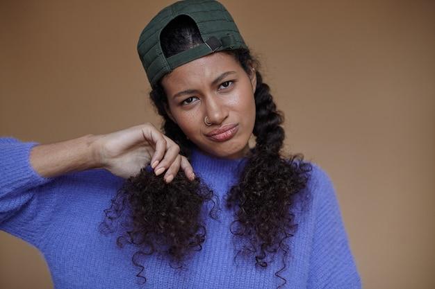 黒い肌の美しい茶色の目の巻き毛のブルネットの女性は、編みこみの髪型を身に着けて、折りたたまれた唇で見て、立っている間カジュアルな服と野球帽を着ています