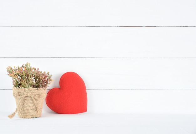 Beautiful brown flower in a pot and red heart on white wooden background