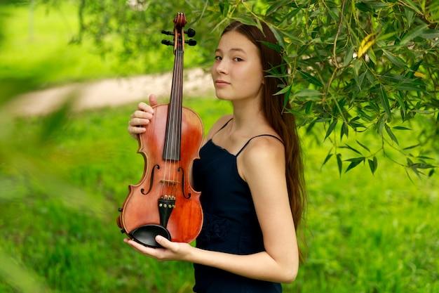 Красивая шатенка азиатской внешности со скрипкой на природе. музыкант по натуре. классическая музыка. фото высокого качества