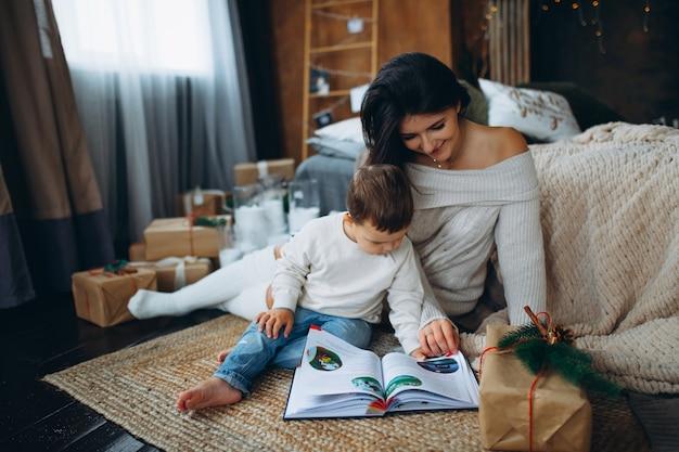 床に座っておとぎ話の本を読んでいる美しい茶髪のお母さんと素敵な男の子の息子