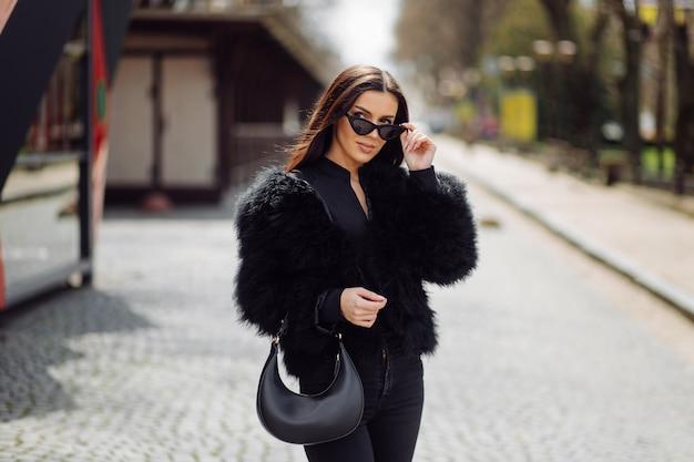 屋外の黒いドレスの美しい茶色の髪のスタイリッシュな女の子。街の通りで春に長い髪の若い魅力的なエレガントな女性の肖像画。