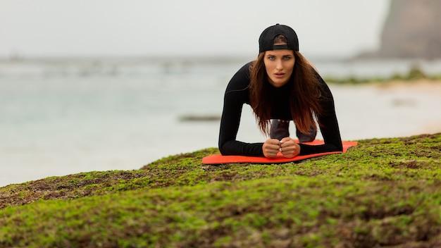 美しい茶色の髪の女性がビーチでスポーツに行きます