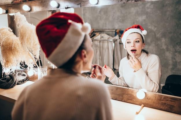 白いセーターの美しい茶色の髪の女性は化粧鏡で見えます