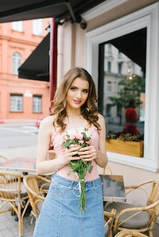 Beautiful brown-haired young girl with a bouquet of roses, professional makeup and styling.