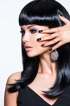 黒い爪と目のファッションメイクで美しい黒髪の女性