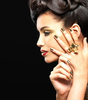 Beautiful brunet woman with golden nails and style makeup of eyes -  on black wall