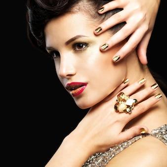 Bella donna brunet con unghie d'oro e trucco stile degli occhi - sul nero