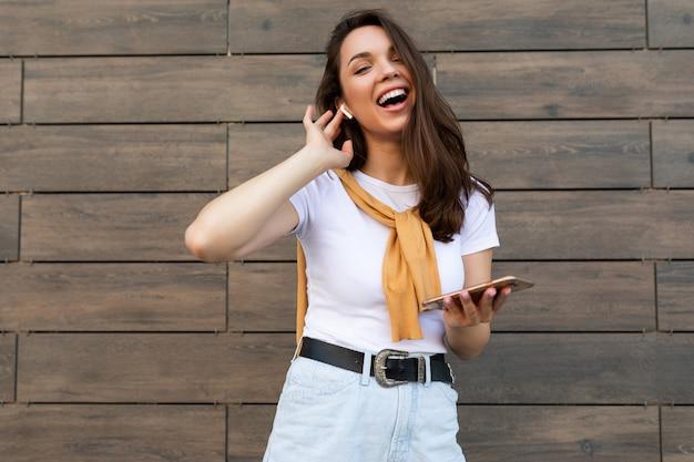 カジュアルな服を着て、通りに立って携帯電話を使って楽しんでいるカメラを見てワイヤレスイヤホンで音楽を聴いている美しい黒髪の若い幸せな女性