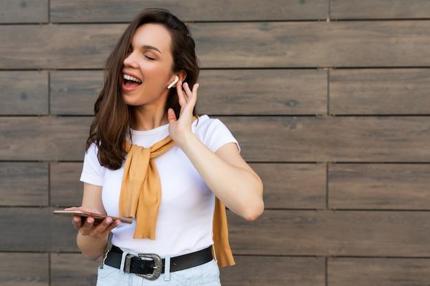 カジュアルな服を着て、ワイヤレスイヤホンで音楽を聴いて美しい黒髪の若い幸せな女性