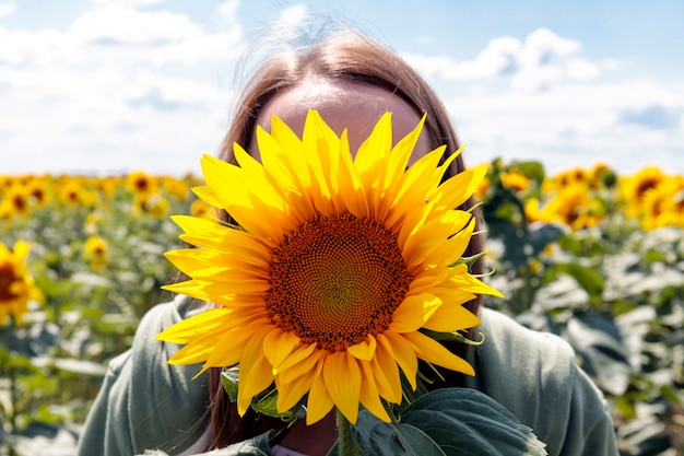Beautiful brunett girl in white dress enjoys and covering face with sunflower.