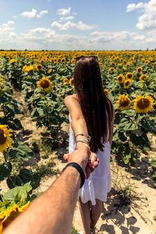 Beautiful brunett girl in white dress hand in hand going to sunflowers field.