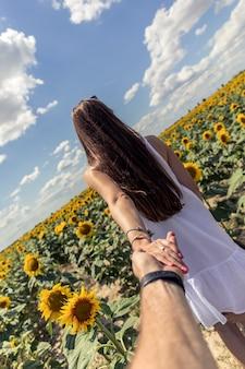 Beautiful brunett girl in white dress hand in hand with husband going to sunflowers field.