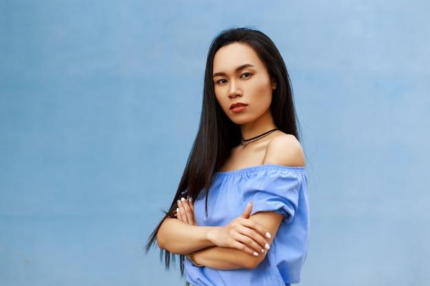 長い髪の美しいブルネットのアジアの女の子は、青に手を組んで手を組んだ。