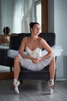 Beautiful brunette ballerina sitting on vintage armchair and adjusting her pointer shoe. copyspace