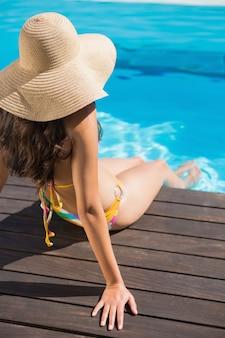Beautiful brunette in bikini sitting by the pool paddling