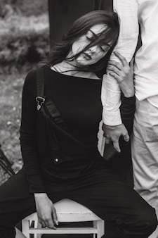 Beautiful brunette in black clothes holds the boy's hand in white