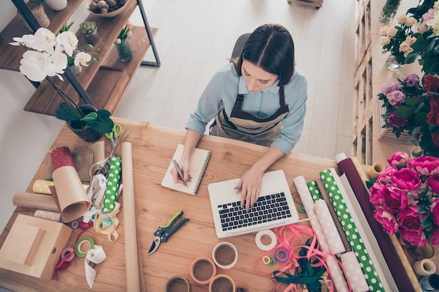 Красивая брюнетка ботаник позирует в своем цветочном магазине с ноутбуком