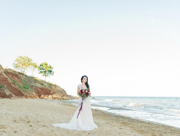 바다 근처 포즈 구슬과 수 놓은 가벼운 쉬폰 웨딩 드레스에 아름 다운 갈색 머리 신부. 해변에서 포즈 럭셔리 드레스에 낭만적 인 아름 다운 신부.