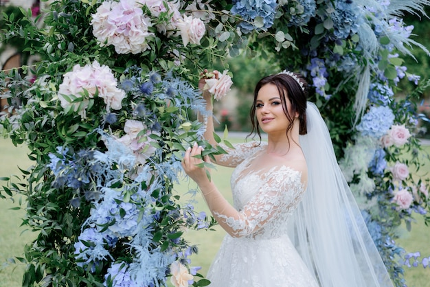 Beautiful brunette bride near the archway made of blue hydrangea and ruscus, wedding day