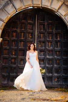 Beautiful brunette bride in white dress posing near old wooden door