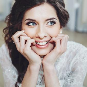 Красивая невеста брюнетка с голубыми глазами в белом платье улыбается невесты. свадебные прически и макияж.