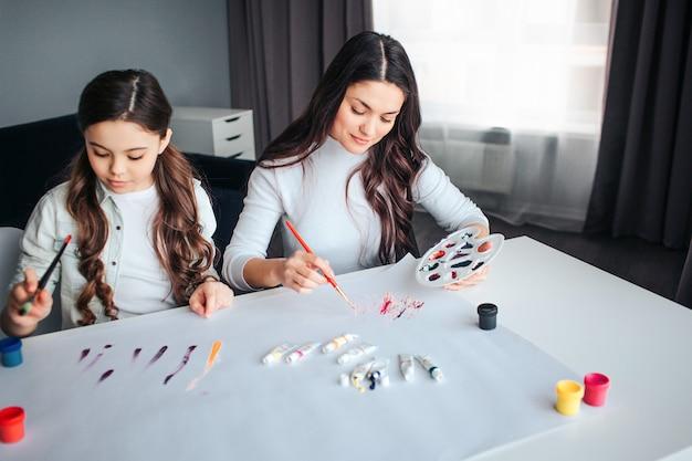 Мать и дочь красивого брюнет кавказские красят совместно в комнате. они сидят за столом и рисуют. спокойные сосредоточенные рабочие.