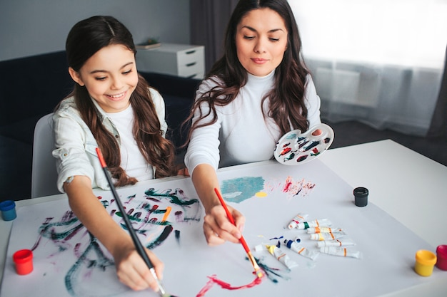 Beautiful brunette caucasian mother and daughter paint together in room. happy girl hold brushes with mom. she smile. young woman has palette in hand. painting heart shape.