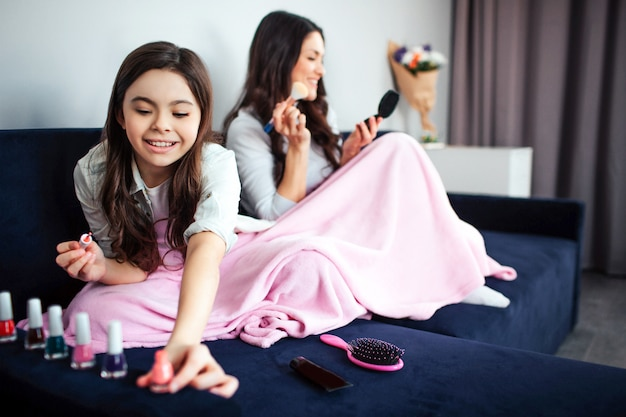 Beautiful brunette caucasian mother and daughter sit together in room. girl reach opened pink nail polish and smile. young woman sit behind and put some make up on face using brush.