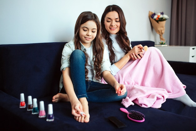 Beautiful brunette caucasian mother and daughter sit together in room. girl use pink nail polish on toes. mom look dowwn at it and smile. they sit together on sofa.