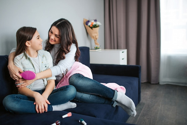 Beautiful brunette caucasian mother and daughter sit together in room. mom hug girl and smile to her. she hold brush.