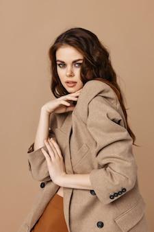 Beautiful brunette in coat fashion glamor home beige