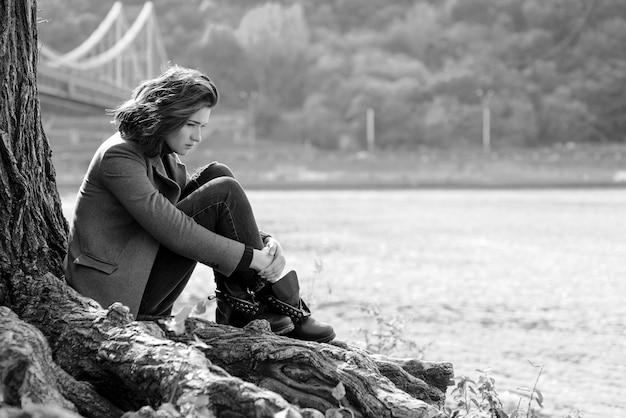 아름 다운 갈색 머리 우울 슬픈 여자 다리 배경에 도시의 강