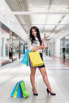Красивая брюнетка делает покупки с помощью кредитной карты