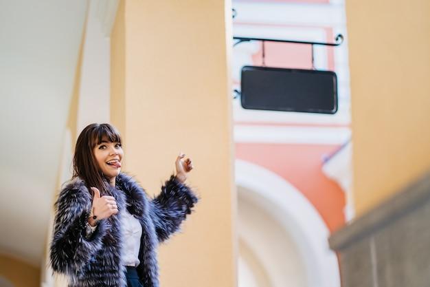 毛皮のコート、白いシャツ、黒いスカートに身を包んだ美しいブルネット。舌が突き出ています。空白の店の看板を指し、もう一方の手で親指を立てます。彼女の買い物に感動 Premium写真