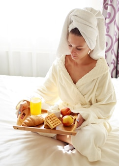 Beautiful brunette in a dressing gown eating breakfast in bed