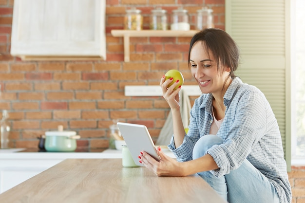 Bella donna castana in abbigliamento casual, si siede in cucina, mangia la mela, utilizza tablet moderno,