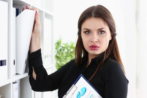 Beautiful brunette female clerk searching for proper document