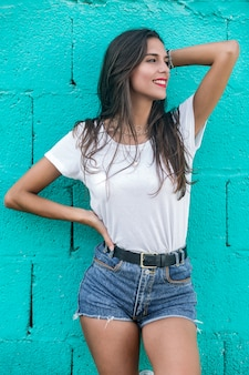 Beautiful brunette female standing by turquoise wall