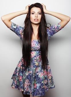Beautiful brunette female in summer dress over white background