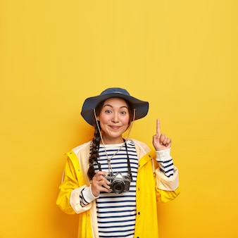 Beautiful brunette female with asian appearance, takes photo during hiking trip with retro camera, wears striped jumper, hat and raincoat, points above with index finger, isolated over yellow wall