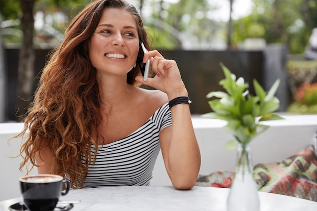 Красивая брюнетка женщина с радостным выражением лица и телефоном в кафе на открытой террасе