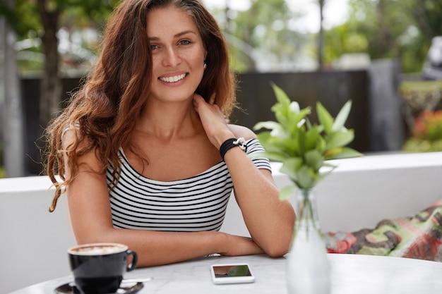 Красивая брюнетка женщина с радостным выражением лица в кафе на открытой террасе