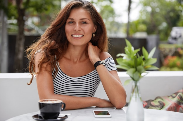 Beautiful brunette female with glad expression in outdoor terrace cafe