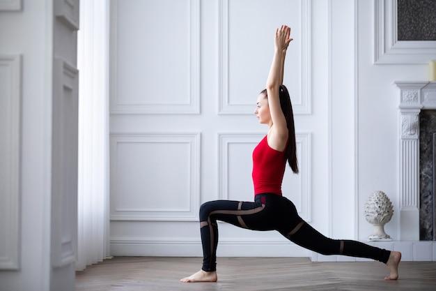 Красивая брюнетка фитнес-модель делает упражнения дома. йога в помещении.
