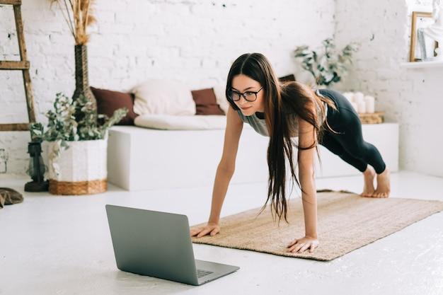 美しいブルネットのフィットネス女性はストレッチ体操をします