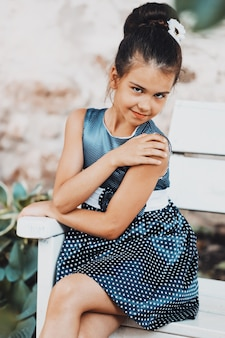 Beautiful brunette girl in a blue polka dot dress in the summer in the park. stylish child in nature. high quality photo