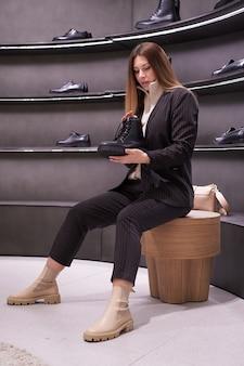 아름 다운 갈색 머리 소녀는 저장소에 신발을 선택합니다.
